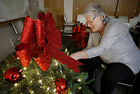 NWA Democrat-Gazette/DAVID GOTTSCHALK Rose Lawrence, administrative assistant to the Mayor  of Springdale, fastens lights Thursday, November 8, 2018, to decorative Christmas baskets at the City Administration Building in Springdale. The handmade baskets will be hung on 22  lamp posts on Emma Avenue in downtown Springdale.