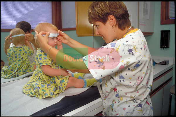 doctor measures head circumference of toddler girl during examination