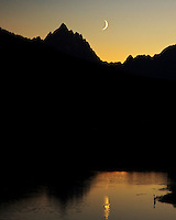 Crecent moon over Oxbow Bend at sunset in Grand Teton National Park. A blue heron fishes in the calm water of the Snake River