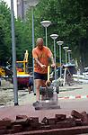 DEN HAAG- Stratenmaker in actie met zware trilmachine. COPYRIGHT TON BORSBOOM