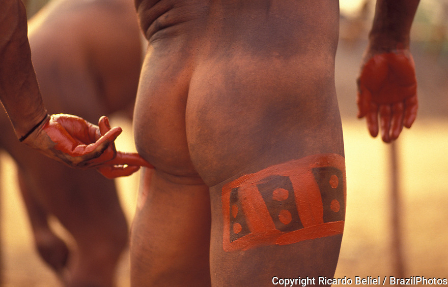 Indigenous People celebrating Yamuricuma Party at Kamayura tribe, a meeting of several indigenous groups from the south part of Xingu river -  body painting with urucum, red-colored plant - Xingu National Park, Amazon, Brazil.
