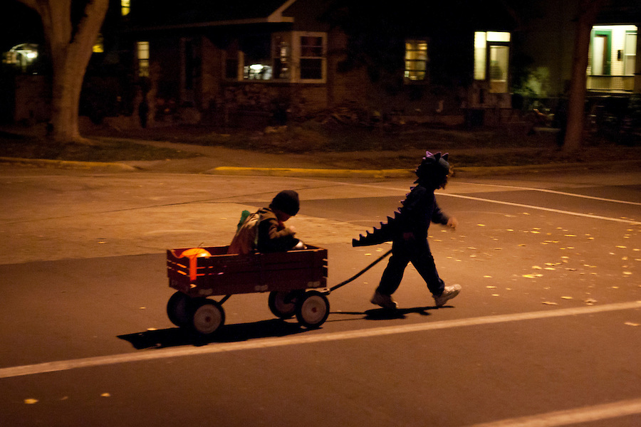 Four-year-old Armine Kashian, dressed as a dinosaur, pulls Holden Miller, also four and wearing a hamburger costume, in a wagon as the two friends go trick-or-treating in Madison, Wis., on Halloween night, Oct. 31, 2011.