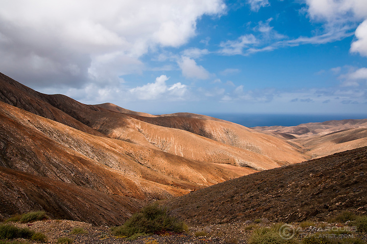 Mountains in Fuerteventura with valley leading to the ocean, Canary Islands, Spain. The west region of Fuerteventura has a very rugged appearance with numerous hills and mountains. Travelling across these mountains is often made on single track roads.