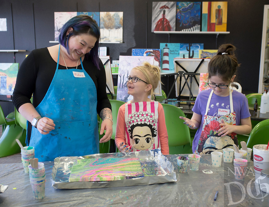 """NWA Democrat-Gazette/CHARLIE KAIJO Art instructor Mallory Gonzalez (left), Grace Cole, 7, of Fayetteville (center) and Aubrey Moses, 11, of Bentonville (right) admire a painting they made during a Spring Break fluid art class, Monday, March 18, 2019 at iPaint in Rogers. <br /><br />Fluid art is any art where the paint moves and creates its own shapes said instructor Sue Mandel. The art uses silicone to create unique and unpredictable designs. """"No one piece will be the same,"""" she said."""