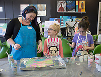 NWA Democrat-Gazette/CHARLIE KAIJO Art instructor Mallory Gonzalez (left), Grace Cole, 7, of Fayetteville (center) and Aubrey Moses, 11, of Bentonville (right) admire a painting they made during a Spring Break fluid art class, Monday, March 18, 2019 at iPaint in Rogers. <br />