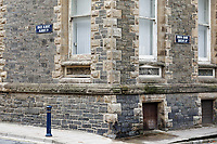 Pictured: Queen's Road (Morfa Mawr) and Albert Place (Maes ALbert) road signs on the old Police Station in Aberystwyth, Wales, UK. Wednesday 28 August 2019<br /> Re: Opened 1866, built by the Hafod Hotel Co as the Queens Hotel; architects, Hayward and Davies; builder George Lumley of Aberystwyth. Sold in 1877 and later converted to local government use; remodelled in1950 by G R Bruce, County Architect.<br /> Detached towards N end of the Promenade, with main entrance to side elevation in Albert Place and rear elevation to Queens Road.<br /> Hotel de Ville style. Asymmetrical 3-storey attic and basement snecked rubble 13-bay W (Promenade) elevation; stepped front with mostly vermiculated dressings, stock brick voussoirs, deep entablature and cornice and cill bands; buttresses to ground floor centre. Steep pitch mansard slate roof with truncated chimney stacks. Dormers with steep overhanging roofs and casement windows; paired to left. 3-bays advanced near the right hand end and with additional storey and splayed angles to 2nd floor (with small cast-iron parapets) and 3rd floor; also to top floor) with small cast-iron parapets) and 3rd floor; also to top floor at the corner. Sash windows, some paired; anthemion panelled cast-iron window box holder across central bays.