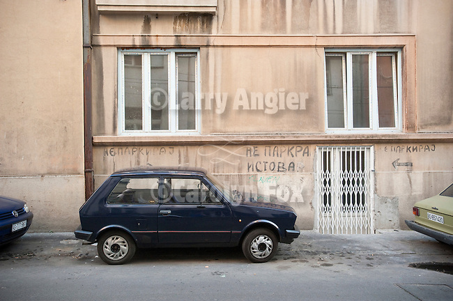 A small, black Zastava coupe parked in a space signed No Parking, Nishka Street, Belgrade, Serbia.