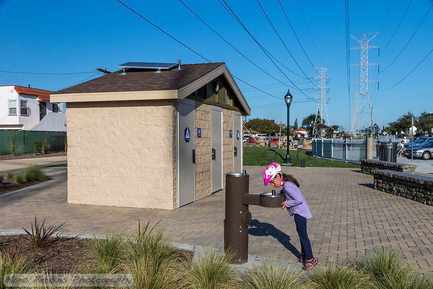 A girl drinks water from the water fountain in front of the bathrooms at State Street Park.  The child is wearing a bike helmet, and standing up on her tiptoes to be able to reach the water fountain.
