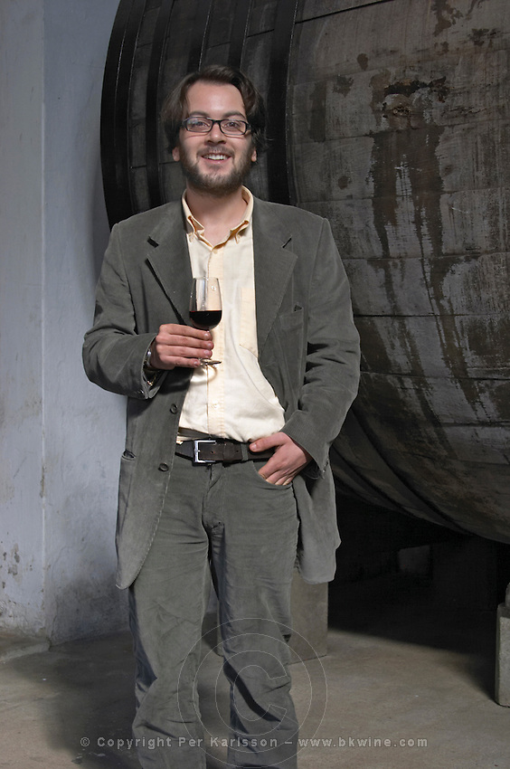 Mr Mendez co-owner and son of Marta Mendez winemaker, holding a glass of wine in the winery in front of an old oak barrel. Bodega Plaza Vidiella Winery, Las Brujas, Canelones, Uruguay, South America