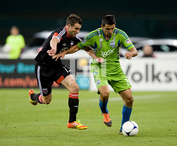Chris Pontius (13) of D.C. United fights for the ball with Leo Gonzalez (12) of the Seattle Sounders during the game at RFK Stadium in Washington DC.   D.C. United tied  the Seattle Sounders, 0-0.