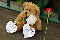 Soft toys and flowers left at the scene in Brithweunydd Road<br /> Re: A woman has been arrested after a child was found dead at a property in Trealaw, Rhondda, Wales, UK.<br /> The woman, aged 37, was detained when emergency services were called to an address in the town at about 10.20am on Friday.<br /> The death is being treated as unexplained.<br /> As part of the investigation, the main route through Trealaw, Brithweunydd Road, has been closed off.