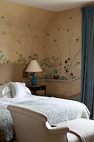 A bedroom decorated with vintage wallpaper depicting a garden scene. A chaise longue stands at the foot of a double bed