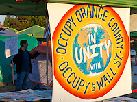 "A man holds a ""Jobs not cuts"" sign and flashes the peace sign behind the ""Occupy Orange County in Unity with Occupy Wall St."" sign at the encampment at Irvine, CA."