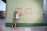 "Attractive local Austin woman poses in front of the famous ""I love you so much"" mural on South Congress (Soco)."