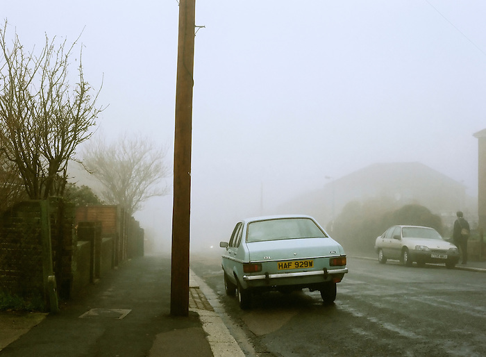 Cars parked on a quiet suburban street on a foggy morning in Brighton. England 1998.