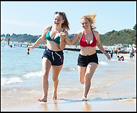 BNPS.co.uk (01202)558833<br /> Pic:   RogerArbon/BNPS<br /> <br /> Georgi Casey (20) and Kieris Castle (19)  cooling off in the sea.<br /> <br /> Brits head to the beach in Bournemouth, ahead of what is predicted to be the hottest bank holiday on record.