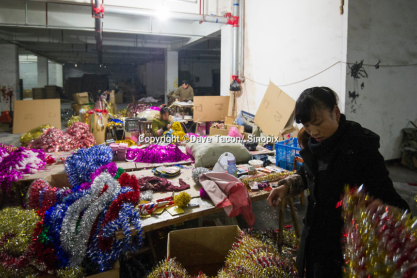 November 28, 2015, Yiwu, China - A young female worker from Yunnan sorts tinsel at the Xin Shua tinsel factory. The factory makes around 30 million RMB (GPB 3.12) of tinsel each year. This worker is paid 0.04 RMB for each bunch of tinsel she tags togther by hand.Photo by Dave Tacon / Sinopix