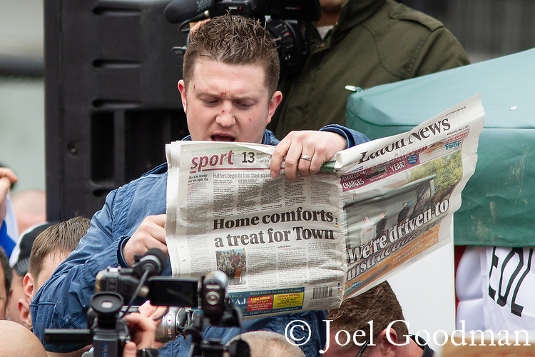 © Joel Goodman - 07973 332324 . 05/05/2012 .  Luton , UK . EDL leader TOMMY ROBINSON ( Stephen Yaxley-Lennon ) holds up a copy of local newspaper Luton News whilst addressing a rally of supporters after the march . Approximately 1,500 people take part in an EDL ( English Defence League ) march in Luton , understood to have been policed by over 1,000 officers . Photo credit: Joel Goodman