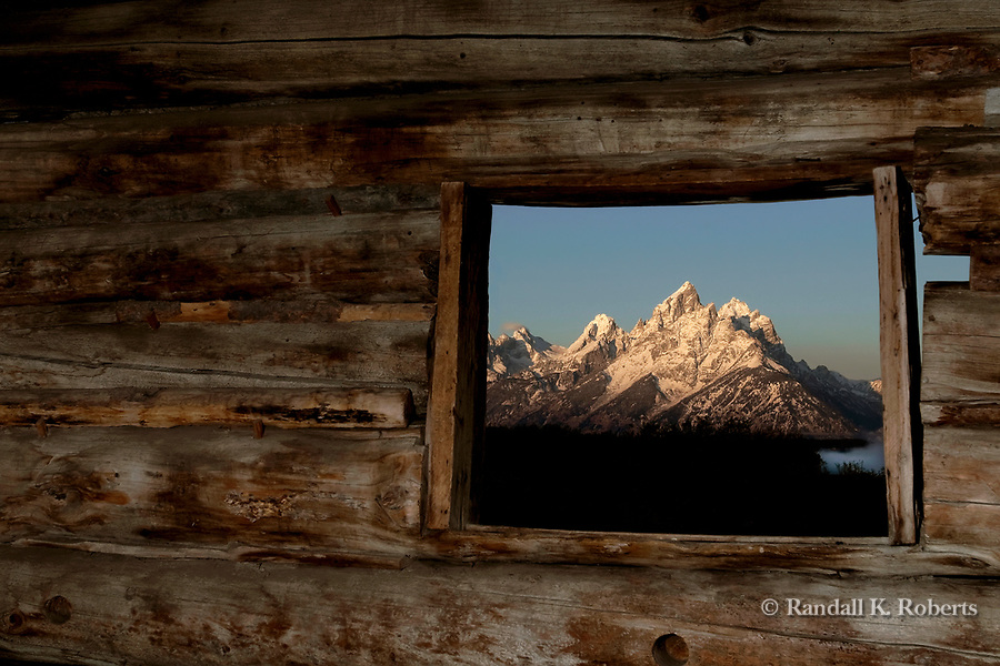 A window in Cunningham Cabin frames the Grand Teton, Grand Tetons National Park, Wyoming