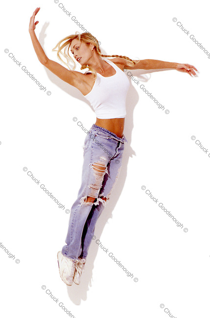 Photo of a Blond Woman Dancer in the midst of a graceful Jump. This is a scan from Grainy film and has some movement. There is a hard shadow against a white wall behind the dancer.