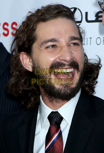 """Shia LaBeouf.""""Lawless"""" premiere held at ArcLight Cinemas, Hollywood, California, USA..August 22nd, 2012.headshot portrait black suit white shirt tie beard facial hair red mouth open smiling  .CAP/ADM/RE.©Russ Elliot/AdMedia/Capital Pictures."""