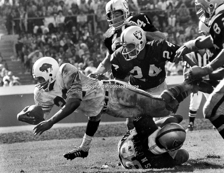 O.J. Simpson tackled by Gerold Irons and Willie Brown..photo by Ron Riesterer
