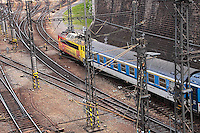 train leaving the main train station. With yellow and orange train and blue and white wagon. Shot from above.