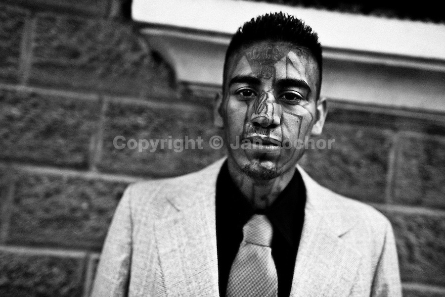 A former member of the 18th Street Gang (M-18) seen on his way to the church in San Salvador, El Salvador, 12 May 2011. During the last two decades, Central America has become the deadliest region in the world that is not at war. According to the UN statistics, more people per capita were killed in El Salvador than in Iraq, in recent years. Due to the criminal activities of Mara Salvatrucha (MS-13) and 18th Street Gang (M-18), the two major street gangs in El Salvador, the country has fallen into the spiral of fear, violence and death. Thousands of Mara gang members, both on the streets or in the overcrowded prisons, organize and run extortions, distribution of drugs and kidnappings. Tattooed armed young men, mainly from the poorest neighborhoods, fight unmerciful turf battles with their coevals from the rival gang, balancing between life and death every day. Twenty years after the devastating civil war, a social war has paralyzed the nation of El Salvador.
