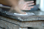 Hands preparing tortillas in a Mayan home in Midway village, Belize