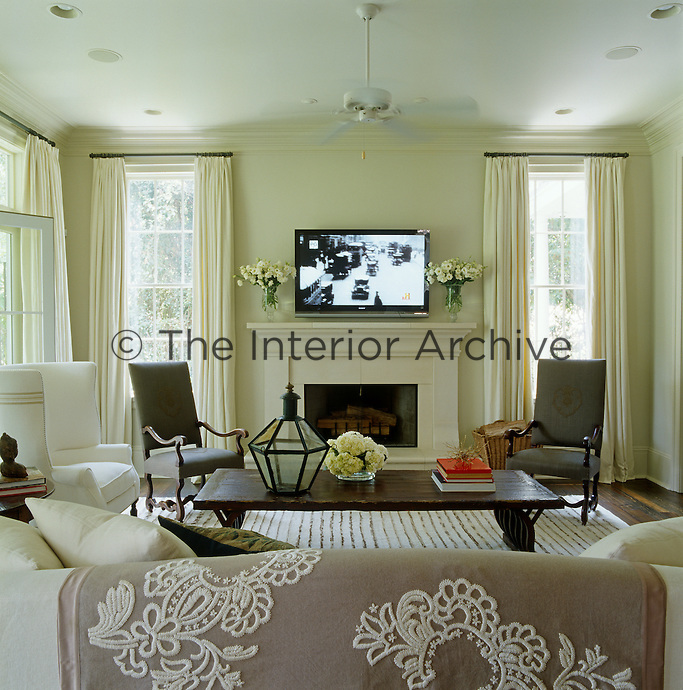 In the family room a flat screen TV hangs above the fireplace framed by a pair of Louis XIV chairs