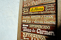 Wooden sign advertising restaurants and shops in Capileira village in the Alpujarras mountains, Andalusia, Spain.