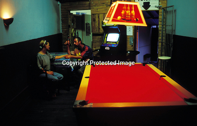 couple,bar,pool table, holding hands,beer, bottle, man,woman, .A homeless couple holds hands and enjoys a beer in a bar in Margate on January 2, 2004 in Margate, South Africa..©Per-Anders Pettersson/iAfrika Photos