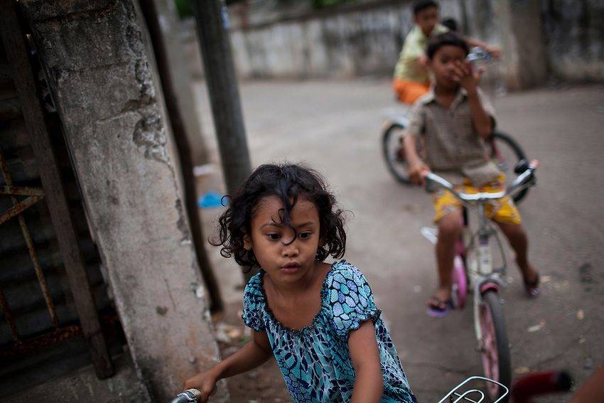 Children ride bicycles through a neighborhood on the edge of Boeung Kak lake in central Phnom Penh, March 5, 2011.