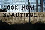 """A message reading """"look how beautiful"""" attached to a fence outside the disused Tempelhof airport in Berlin, Germany. The historic airfield was constructed in 1923, used by the Nazis for rallies and became the site of the American airlift during the blockade of West Berlin  by the USSR. In October 2015, giant hangars were converted into temporary accommodation space for hundreds of refugees arriving in Berlin."""