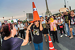 26 MAY 2014 - BANGKOK, THAILAND:  Women dance with traffic cones on their heads on Phaya Thai Road during a protest against the coup in Thailand at Victory Monument during a pro-democracy rally in Bangkok. Traffic cones have emerged as a symbol of the pro-democracy movement because guards from the anti-government forces protesting in Bangkok beat and hospitalized several people who moved traffic cones the guards put out. About two thousand people protested against the coup in Bangkok. It was the third straight day of large pro-democracy rallies in the Thai capital as the army continued to tighten its grip on Thai life.  PHOTO BY JACK KURTZ