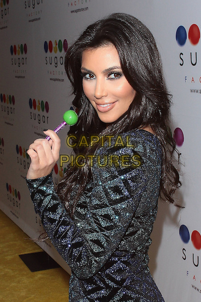 KIM KARDASHIAN .Mel B's Sugar Factory Couture Lollipop Series Launch Party at Guys and Dolls Lounge, West Hollywood, California, USA. .January 19th, 2010 .half length black beads beaded dress blue sweet candy sequins sequined looking over shoulder .CAP/ADM/TC.©T. Conrad/AdMedia/Capital Pictures.