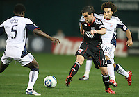 Chris Pontius #13 of D.C. United moves the ball between Kevin Alston #30 and Emmanuel Osei #5 of the New England Revolution during an MLS match on April 3 2010, at RFK Stadium in Washington D.C.