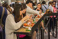 Visitors to Chelsea Market in New York devour lobsters from The Lobster Place on Friday, May 17, 2013. The market is a favorite destination for tourists and locals alike abounding in a myriad collection of restaurants and other food related businesses. The market is a destination for food tours as well as individuals looking to sample.  (© Richard B. Levine)
