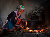 An old women from the Flower-Hmong at her stove preparing for food in her home. North Vietnam,