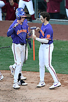 Shortstop Logan Davidson (8) of the Clemson Tigers, left, is handed the sledge hammer by Bryce Teodosio after hitting a two-run home run in the eighth inning of the Reedy River Rivalry game against the South Carolina Gamecocks on Saturday, March 2, 2019, at Fluor Field at the West End in Greenville, South Carolina. Clemson won, 11-5. (Tom Priddy/Four Seam Images)