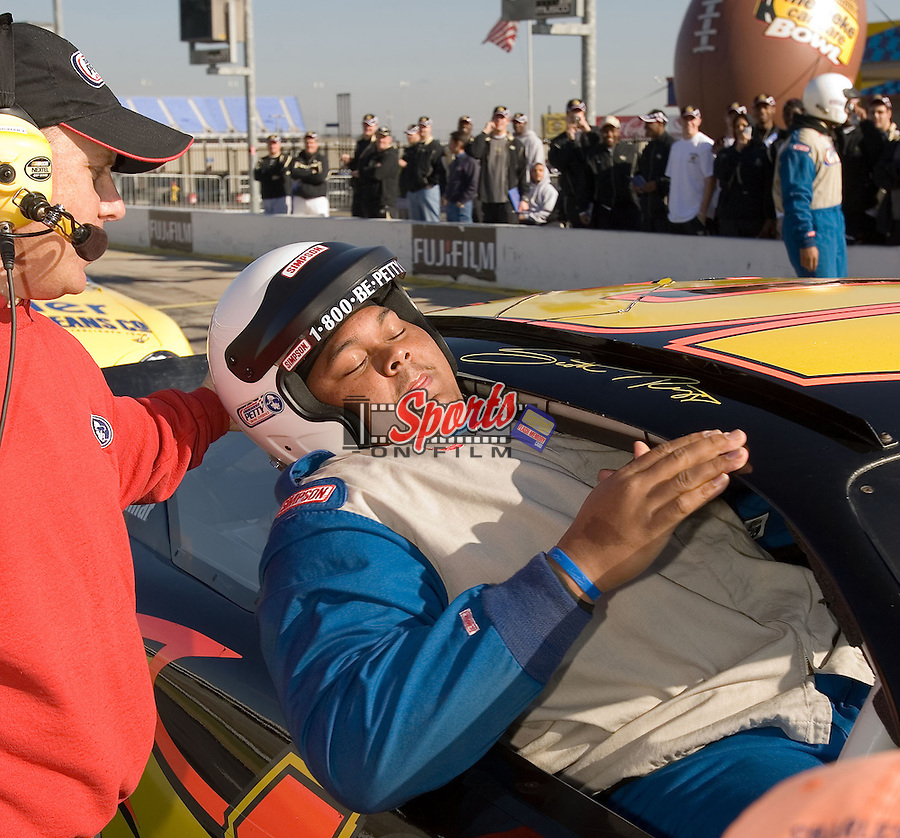 """Chris DeGeare, a 6' 4"""" 360 pound offensive guard for the Wake Forest Demon Deacons, climbs out of the passenger side window of a race car at the Richard Petty Driving Experience at Lowe's Motor Speedway Thursday, December 27, 2007 in Concord, NC."""