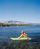 CROATIA, Korcula, Dalmatian Coast, a boy paddling his board along the shore in Korcula.