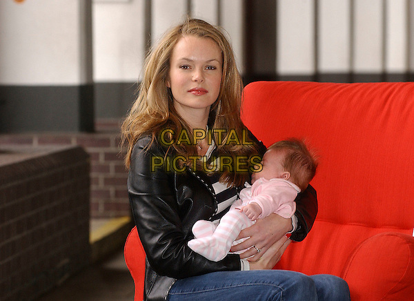 AMANDA HOLDEN & LEXI.The final celebrity to be photographed for an awareness raising exhibition for Shelter's Red Chair Sit in. Amanda brought her 9 week old Daughter Lexi along to the shoot at The Gallery, Oxo Tower Wharf, London, UK..March 29th, 2006.Ref: BEL.half length sitting black leather jacket baby child mother family.www.capitalpictures.com.sales@capitalpictures.com.© Capital Pictures.