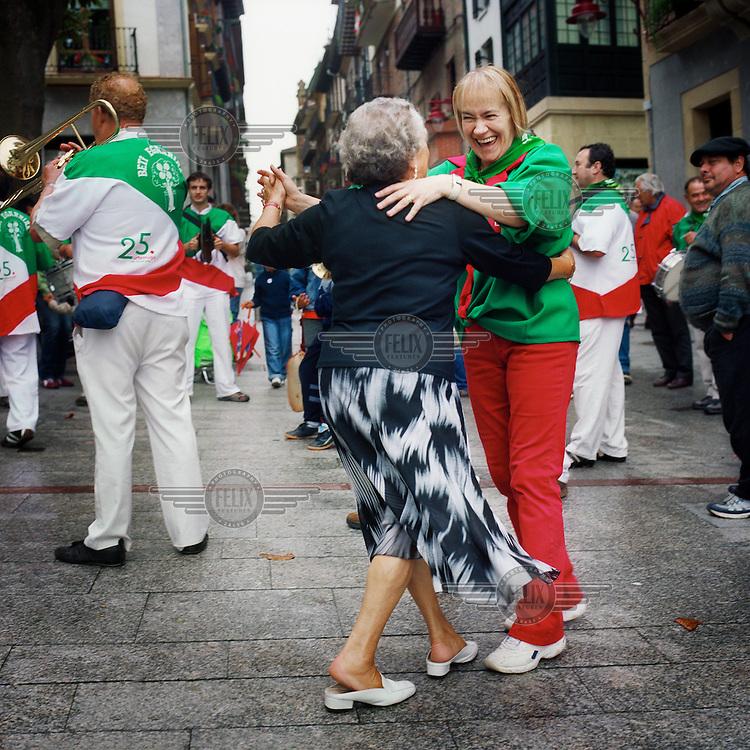 Two women dance in the street during the festival of Saint John.