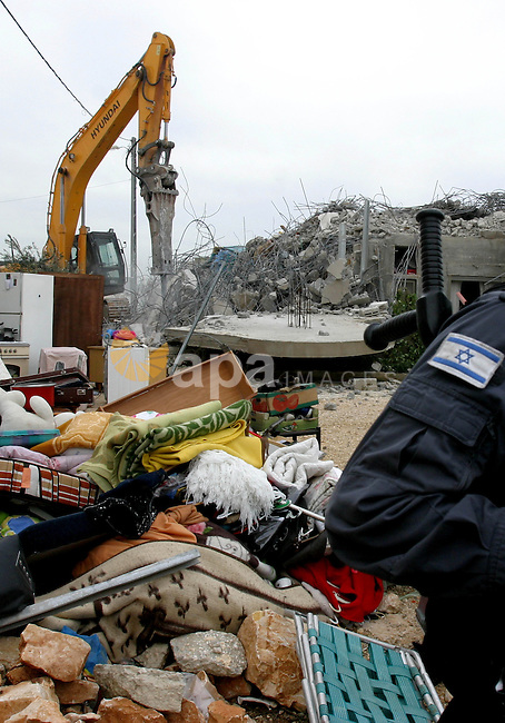 An Israeli bulldozer destroys a Palestinian house in the Arab east Jerusalem neighborhood of Beit Hanina on February 5, 2013. Palestinian homes built without a construction permit are often demolished by order of the Jerusalem municipality. Photo by Mahfouz Abu Turk
