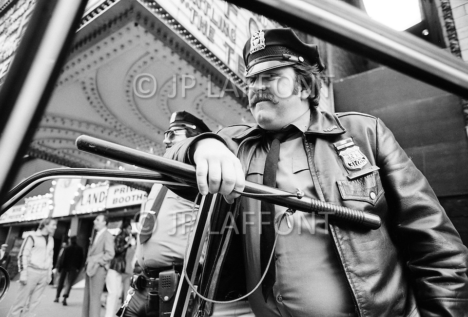 May, 1980. Manhattan, New York City, NY. Two NYPD police officers keep a watchful eye and batons at the ready while on patrol in Times Square. The area, once a cultural hub, full of theaters, music halls and upscale hotels, declined into a world of sex, drugs and crime and sleazy businesses.<br /> <br /> Manhattan, New York City, NY, Mai, 1980. 23heures : Deux policiers patrouillent Times Square, le quartier est dangereux. La proximit&eacute; des sex-shops, les cin&eacute;mas pornographiques, la prostitution et les tripots, furent les facteurs de la d&eacute;t&eacute;rioration du quartier.