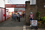 A programme seller outside the entrance to the New Road stand entrance pictured before Brentford hosted Leeds United in an EFL Championship match at Griffin Park. Formed in 1889, Brentford have played their home games at Griffin Park since 1904, but are moving to a new purpose-built stadium nearby. The home team won this match by 2-0 watched by a crowd of 11,580.