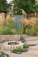 Garden Firepit fireplace of brick, with pebble patio in circular with pathway, wall, ornamental grasses, thymus, herbs, rosmarinus rosemary, Achillea, dry garden, using mixed hardscaping, garden door and arbor
