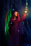 Artistic fairy tale portrait of a woman in a red hooded dress with a lantern in a forest at night with fireflies around and a tree trunk illuminated from the inside behind her. Witch or fairy. Halloween mysterious concept.