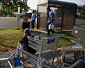 Shopping carts are substituted for benches as a group waits for the number ten D.A.T.A. bus outside of K-Mart along University Drive in Durham.